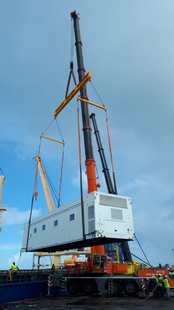 Mobile healthcare facility is lifted by crane at Caribbean port