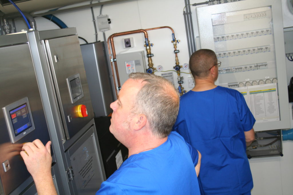 Estates workers checking the Endoscope Decontamination Unit technical room